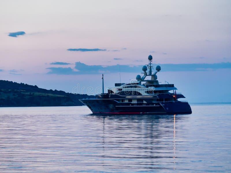 Barco luxuoso moderno do cruzador do motor ancorado na baía no alvorecer, Grécia fotografia de stock royalty free