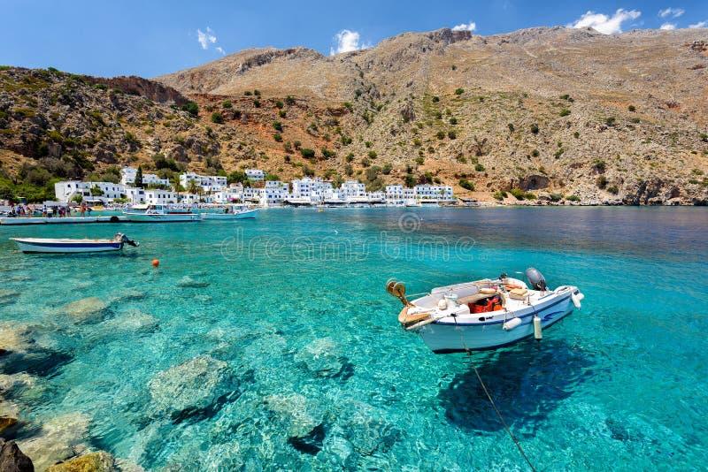 Barco a motor pequeno na baía clara da água da cidade de Loutro na ilha da Creta, Grécia imagem de stock