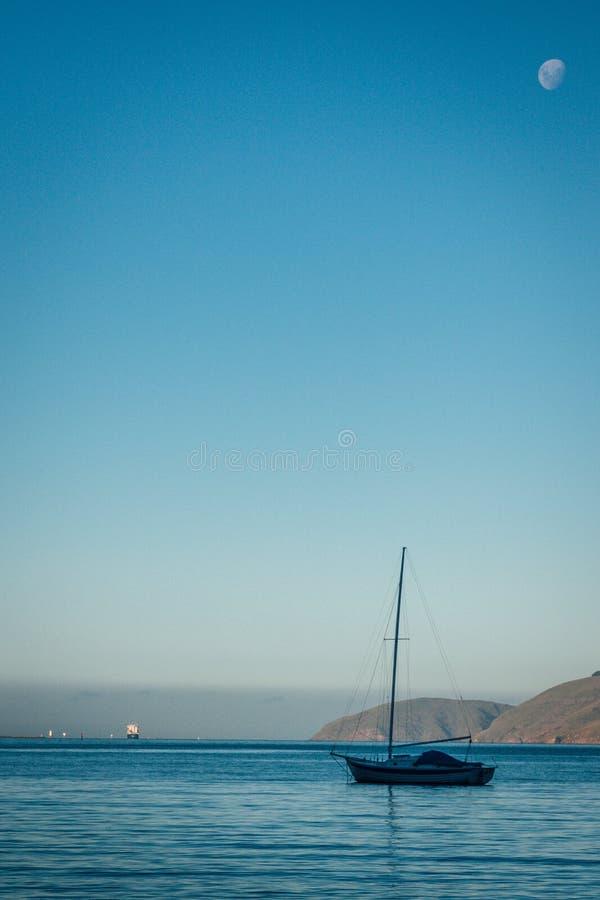 Barco na água com a lua no céu fotos de stock royalty free