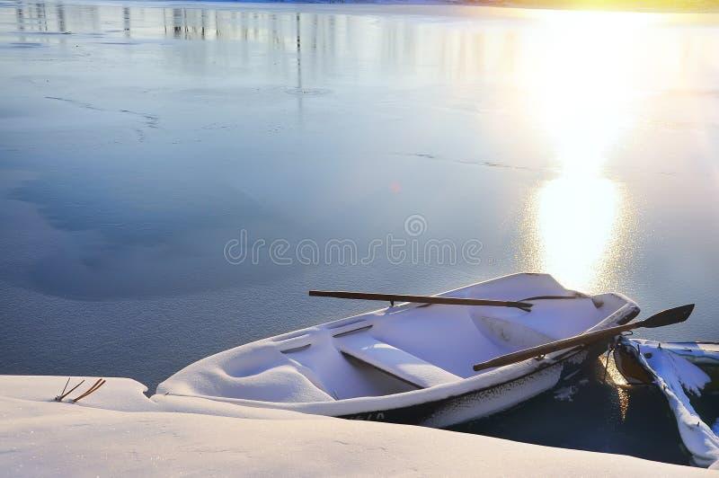 Barco na neve no alvorecer no rio no inverno imagens de stock royalty free