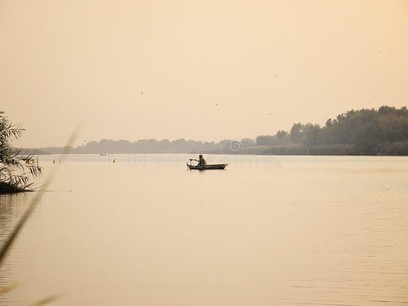 Barco no lago calmo com pescador e junco no nascer do sol imagem de stock