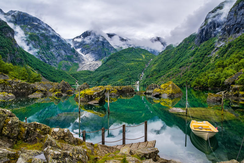 Barco no lago em um fundo das montanhas e da geleira Norwa fotografia de stock