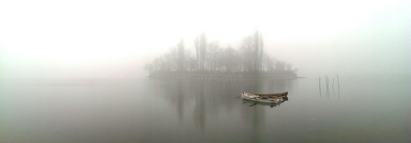 Barco no lago enevoado imagem de stock