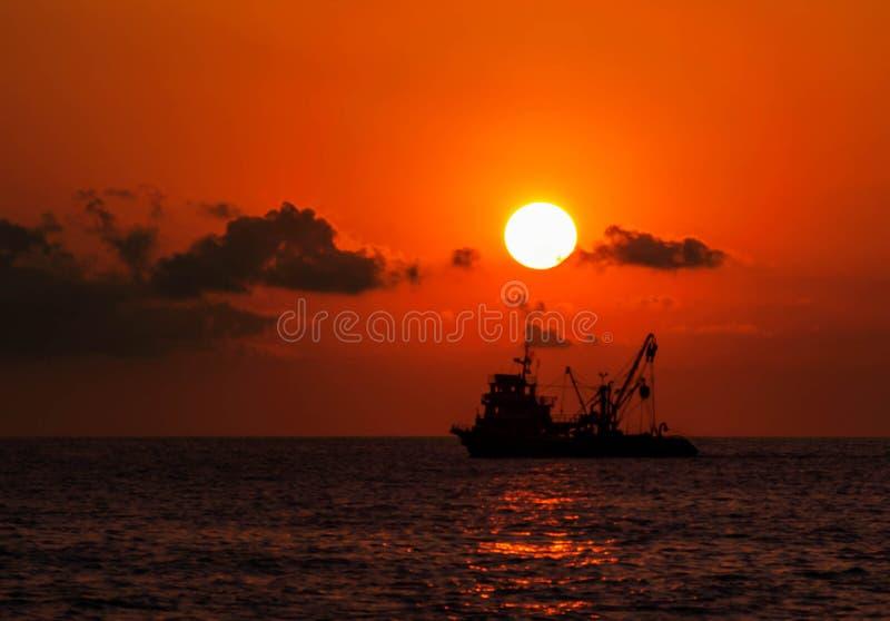Barco no mar aberto durante um por do sol imagem de stock royalty free