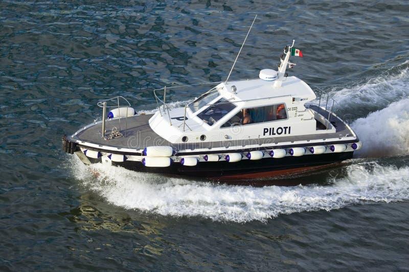 Barco piloto que acompanha o navio de cruzeiros fora do porto no porto de Civitavecchia, Itália, o porto de Roma imagem de stock