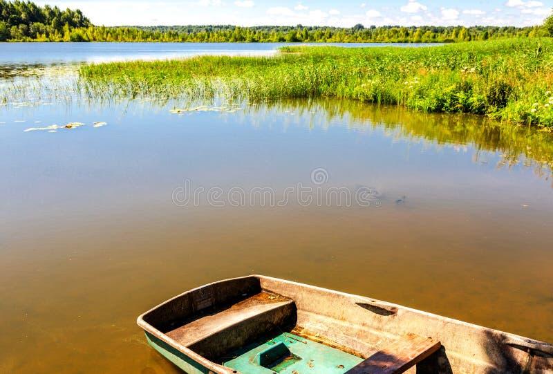 Barco plástico no banco do lago fotos de stock