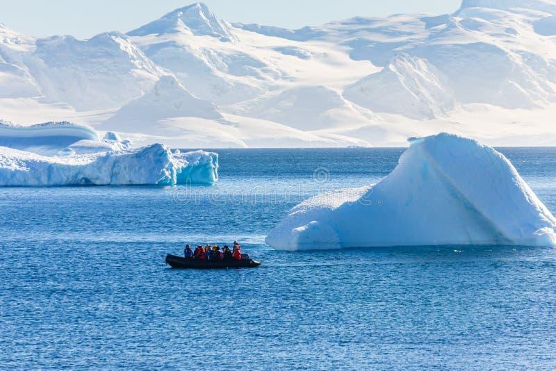 Barco por completo de los turistas que pasan por los icebergs enormes en el ne de la bahía imagenes de archivo