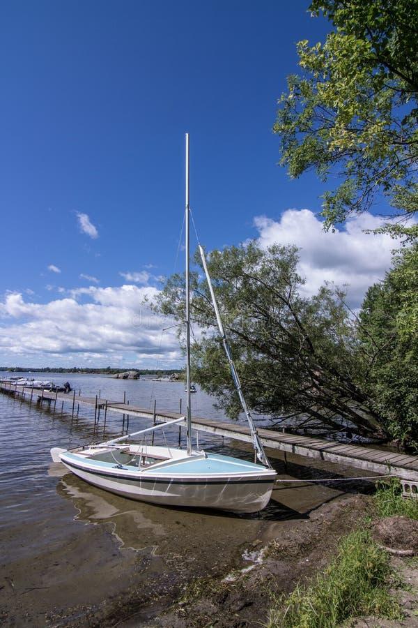 Barco por un muelle en una cabaña en Muskoka, Ontario, Canadá imagenes de archivo