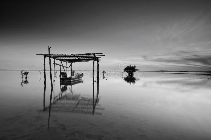 Barco preto e branco do pescador durante o nascer do sol na praia Kelantan malaysia de Jubakar Foco macio devido à exposição long foto de stock royalty free