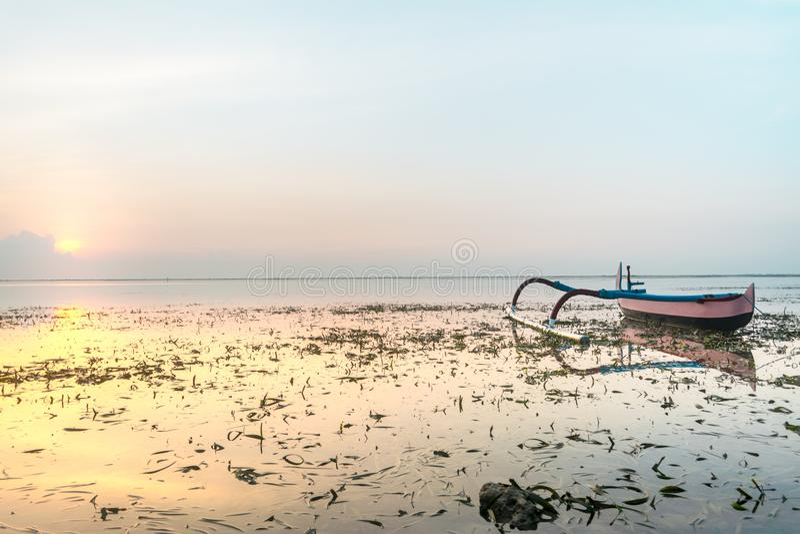 Barco que ancla cerca de la playa o de la costa llena de alga marina en la salida del sol o la puesta del sol con el reflejo de l imágenes de archivo libres de regalías