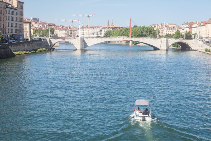 Barco que aproxima a ponte de Pont Bonaparte de Saone River perto do riverbank e do beira-rio de Quais de Saone no centro da cida imagens de stock