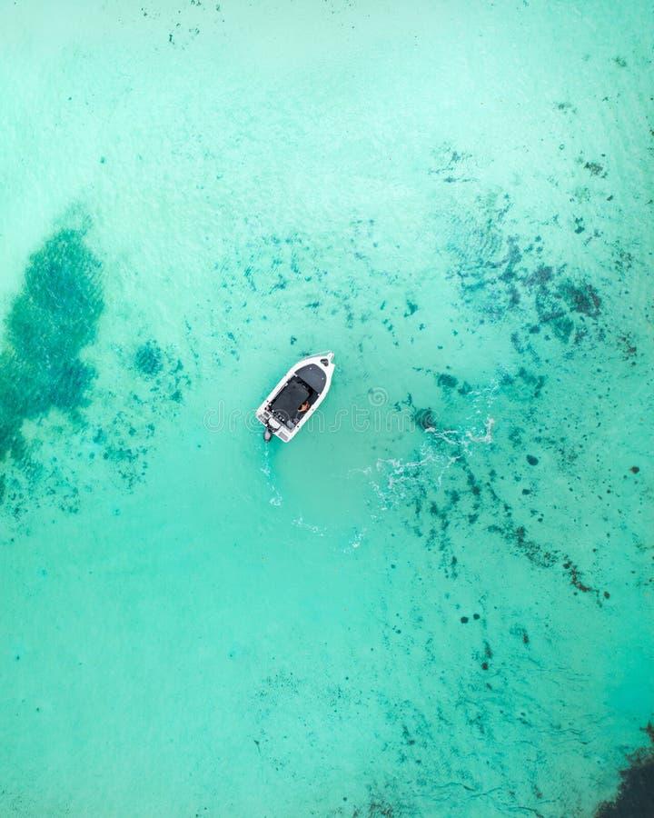 Barco que cruza a través del agua azul en la salida del sol imagen de archivo