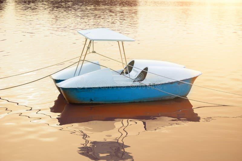 Barco que flutua sobre a água da pele com escape claro do por do sol como o CCB foto de stock