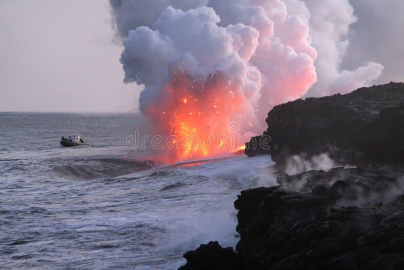 Barco que mira a Lava Flow Into Pacific Ocean fotografía de archivo