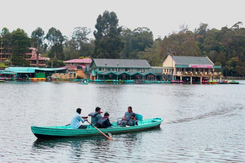 Barco que monta uma família no lago do kodaikanal perto da casa de barco imagens de stock royalty free