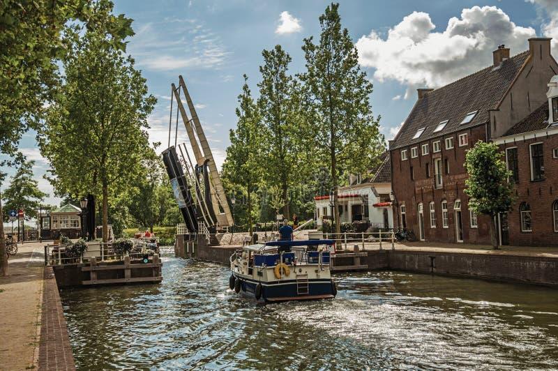 Barco que passa por um canal largo árvore-alinhado no dia ensolarado em Weesp foto de stock