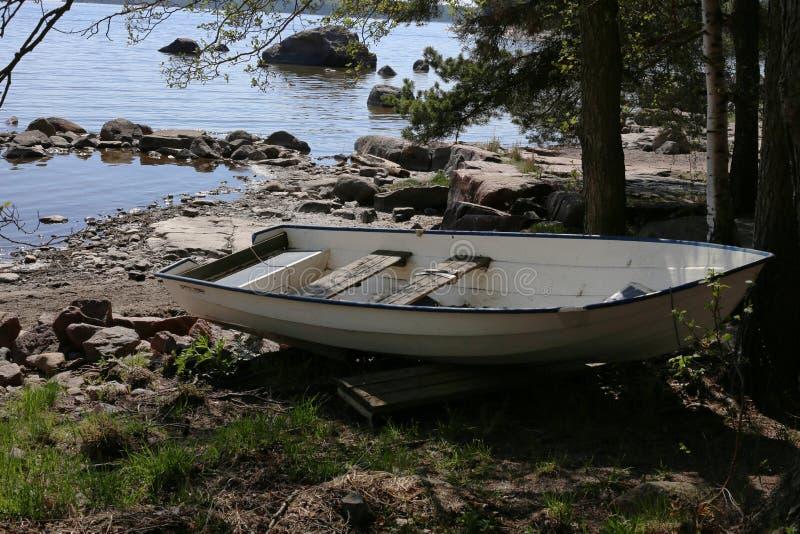 Barco que rema de madera en la costa del mar Báltico durante la primavera foto de archivo