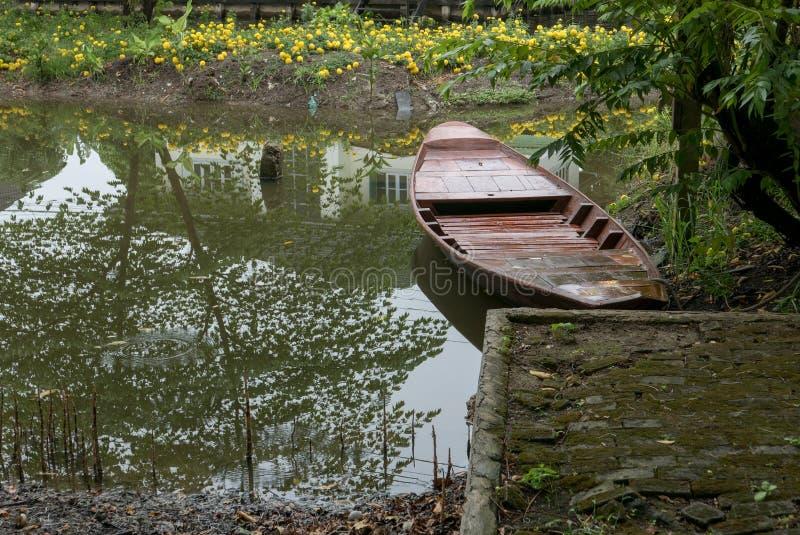 Barco que rema en el río apacible; pequeño bote de remos amarrado en riverbank fotos de archivo