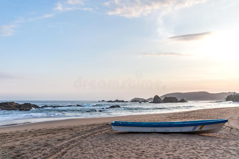 Barco que rema en una playa arenosa sola en el Océano Pacífico durante la puesta del sol imágenes de archivo libres de regalías