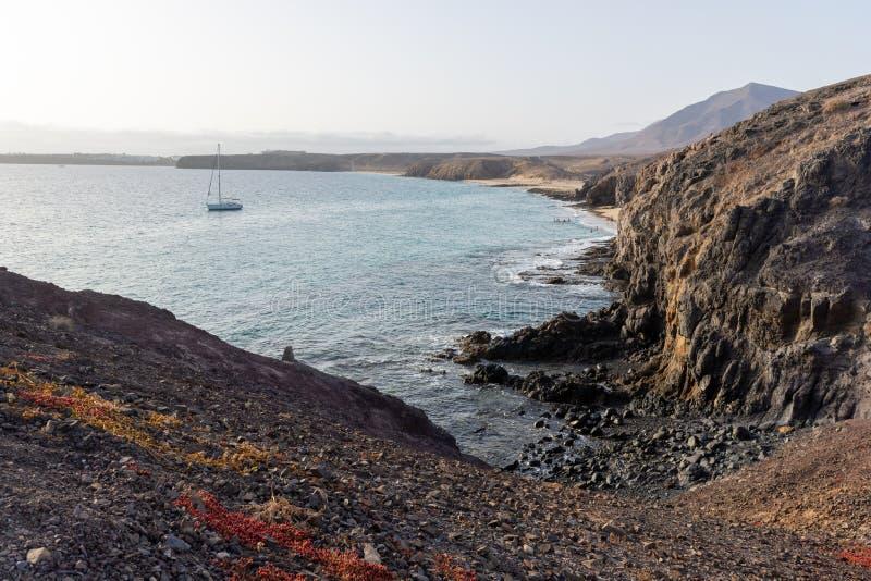 Barco que sae da costa rochosa, Lanzarote, Ilhas Canárias fotos de stock royalty free