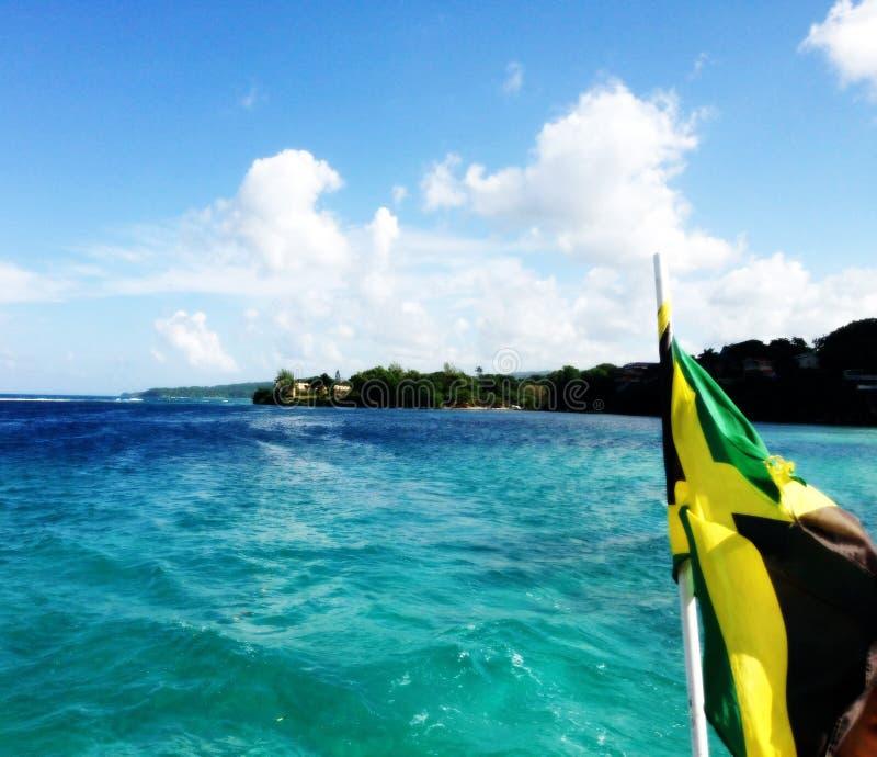 Barco que se arrastra de la bandera jamaicana en el océano foto de archivo