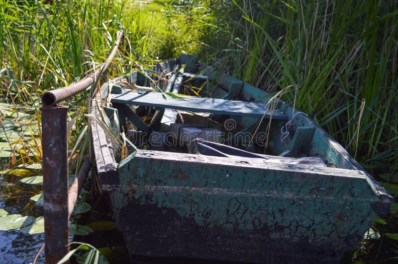 Barco quebrado dilapidado lamentable de madera viejo para nadar en los bancos del río, del lago, del mar en la hierba y de cañas  foto de archivo