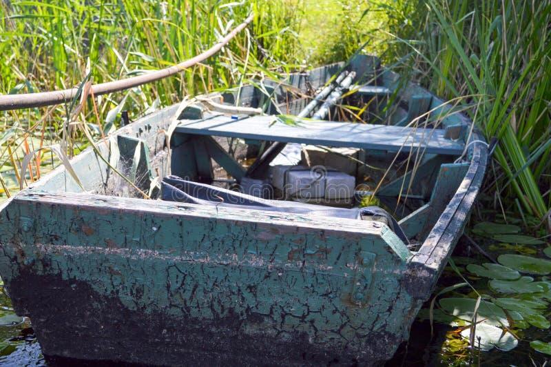 Barco quebrado dilapidado lamentable de madera viejo para nadar en los bancos del río, del lago, del mar en la hierba y de cañas  imagen de archivo libre de regalías