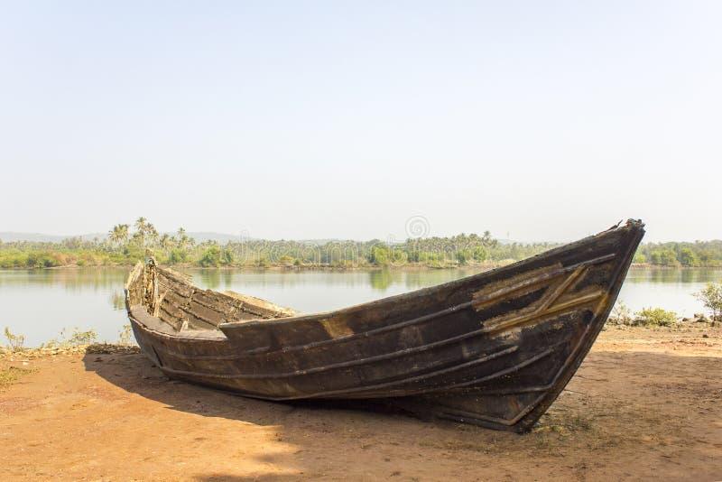 Barco quebrado velho na costa contra o contexto do rio e da selva verde imagens de stock
