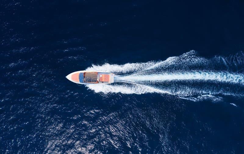 Barco rápido en el mar en Bali, Indonesia. Vista aérea de un barco flotante de lujo en aguas azules transparentes en un día sol fotografía de archivo libre de regalías