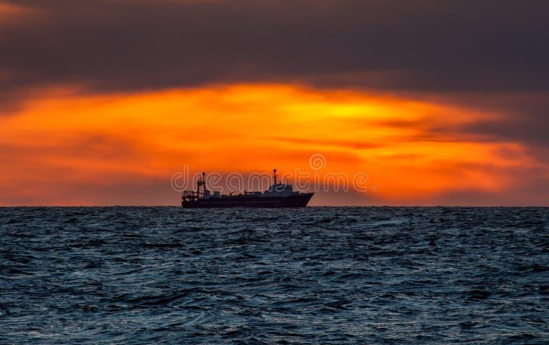 Barco rastreador de la pesca en puesta del sol imagen de archivo libre de regalías