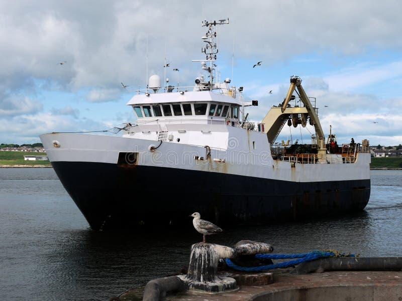 Barco rastreador severo que llega el puerto imagen de archivo libre de regalías
