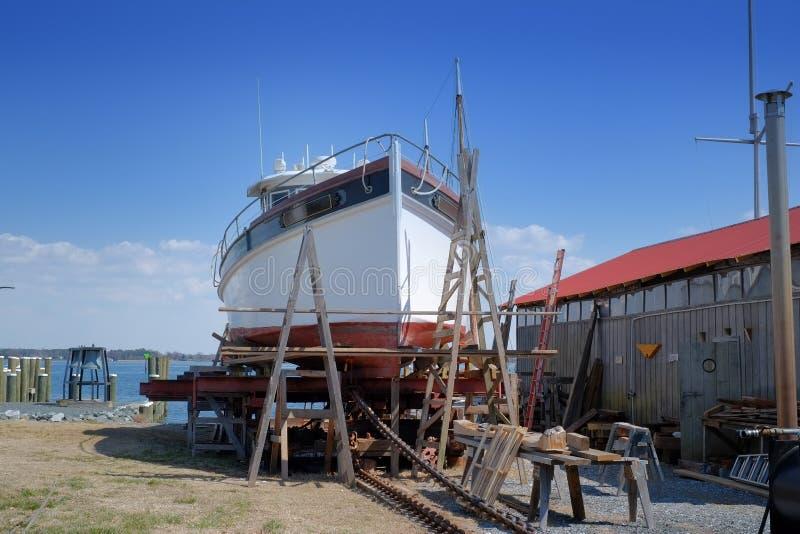 Barco rastreador viejo de la pesca que es restaurado en vieja yarda del barco fotos de archivo libres de regalías