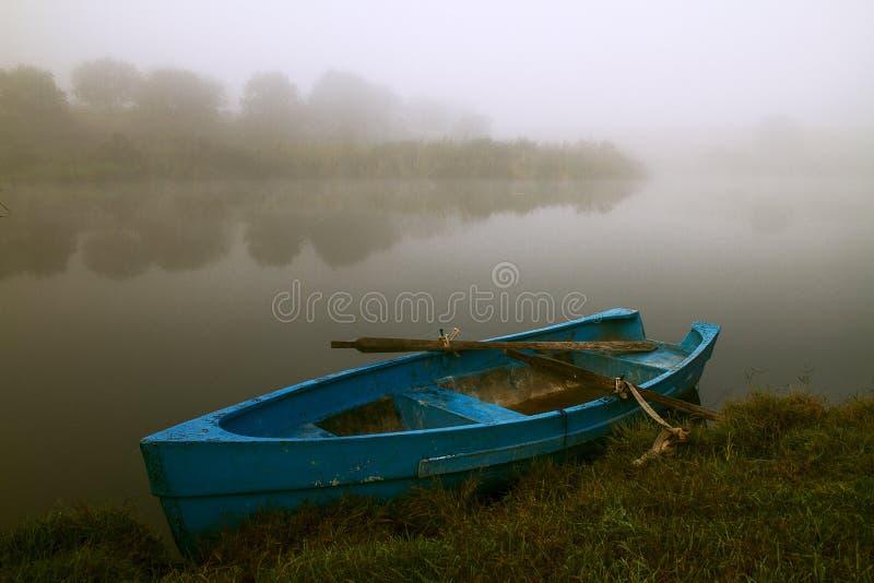 Barco a remos azul na névoa fotografia de stock royalty free