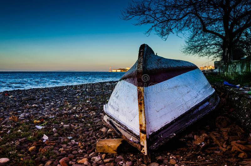 Barco a remos invertido dos pescadores na costa do por do sol imagens de stock royalty free