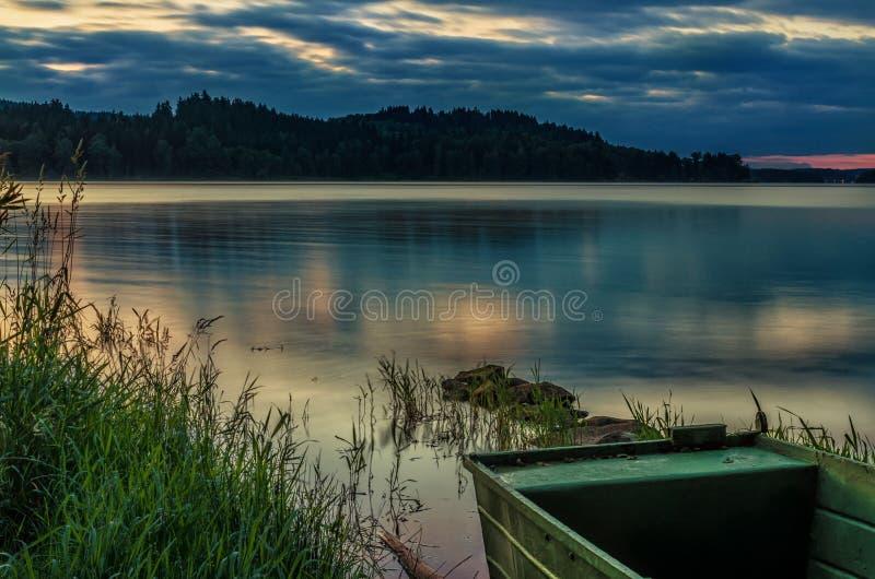 Barco a remos no lago bonito com sunse dramático fotos de stock