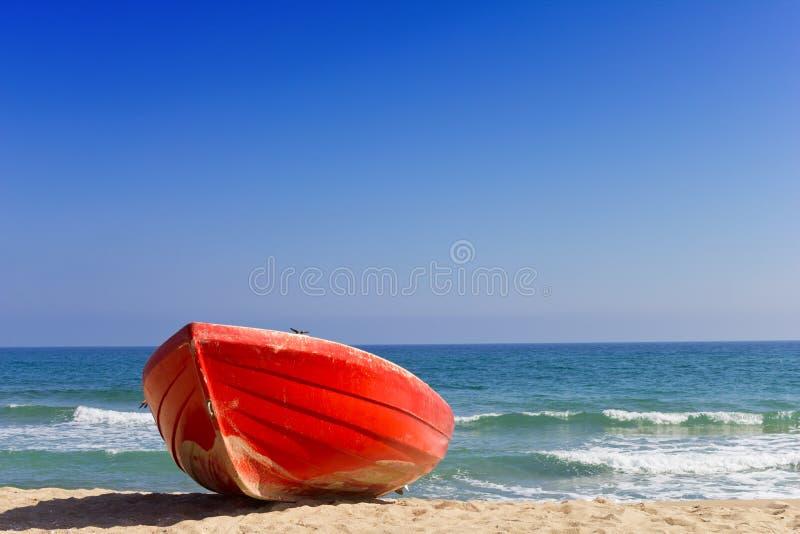 Barco rojo en la playa imagenes de archivo