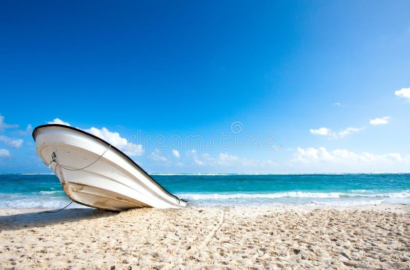 Barco só em uma praia tropical fotografia de stock royalty free