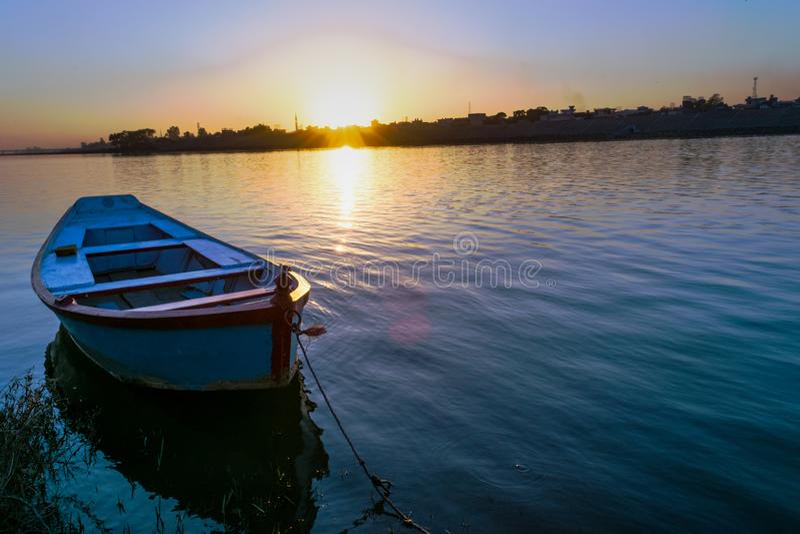 Barco só na água com por do sol de surpresa fotos de stock