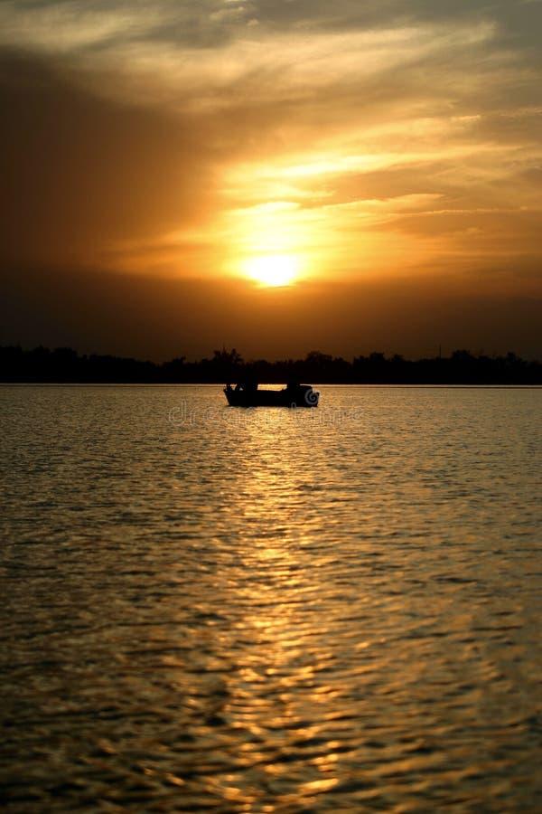 Barco sob um por do sol fotografia de stock royalty free