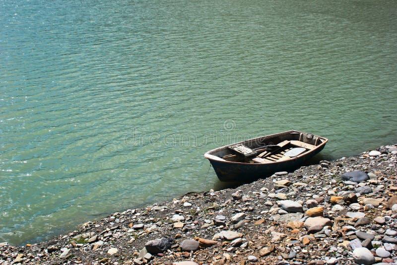 Barco solitario de la batea en orilla rocosa del lago fotos de archivo
