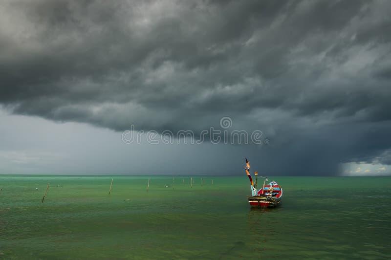 Barco solo con la nube de lluvia fotografía de archivo