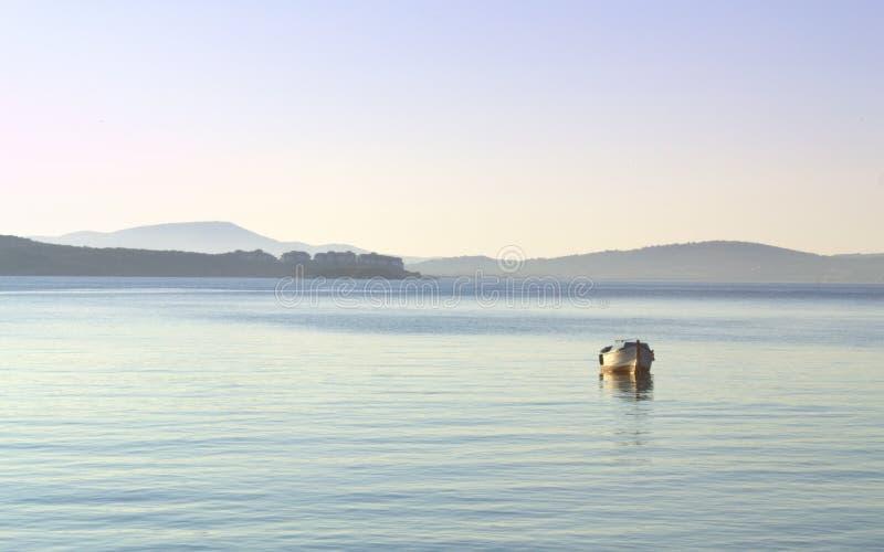 Barco solo en agua tranquila fotos de archivo
