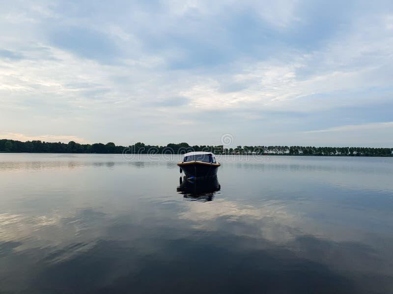 Barco solo en el lago, madrugada imagenes de archivo