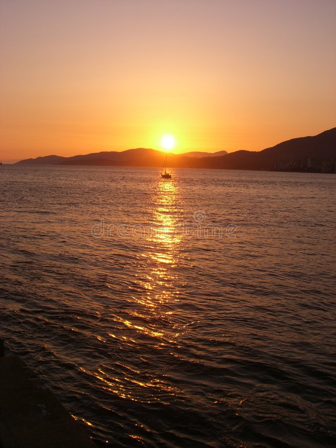 Barco solo en la puesta del sol imagen de archivo