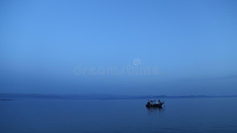 Barco sozinho no azul imagens de stock royalty free
