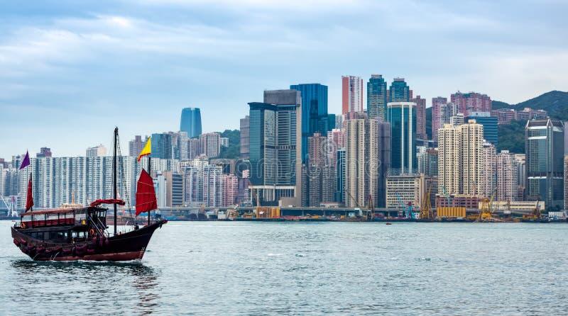 Barco tradicional chinês da sucata na frente da skyline de Hong Kong imagens de stock