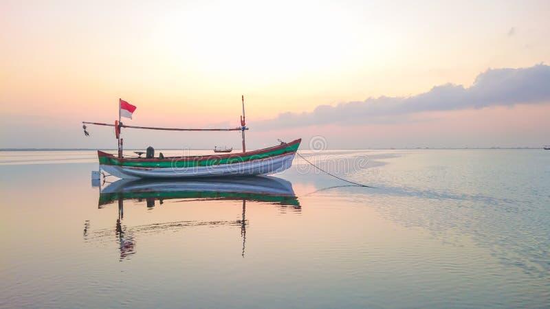 Barco tradicional de Indonesia en la puesta del sol fotos de archivo