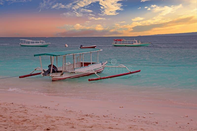 Barco tradicional en la playa de la isla de Gili Meno, Indonesia en la puesta del sol foto de archivo libre de regalías