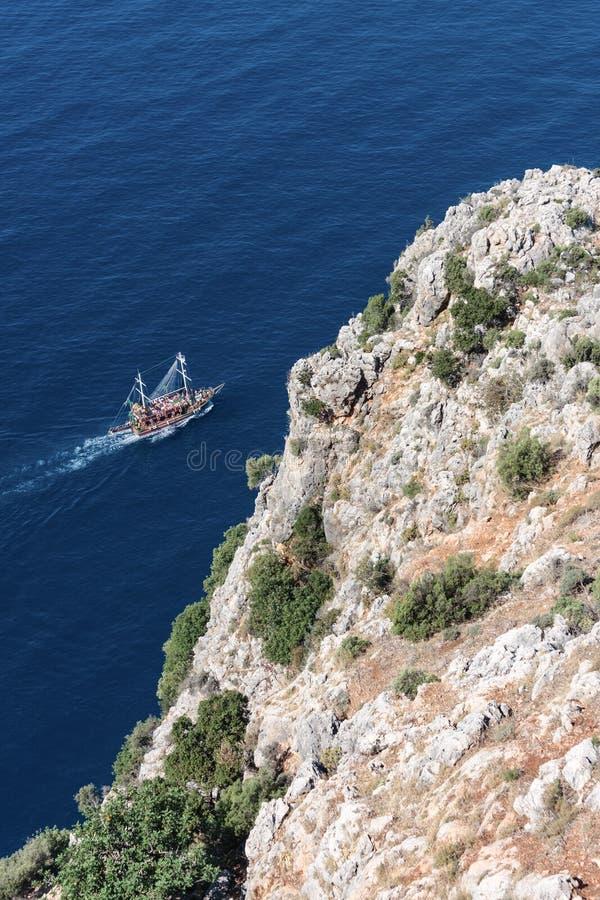 Barco turístico que passa pela rocha fotografia de stock royalty free