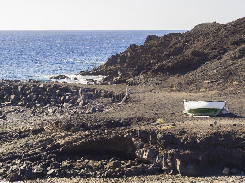 Barco verde blanco en costa rocosa de la roca de la lava de la orilla de mar en Tenerife imagen de archivo